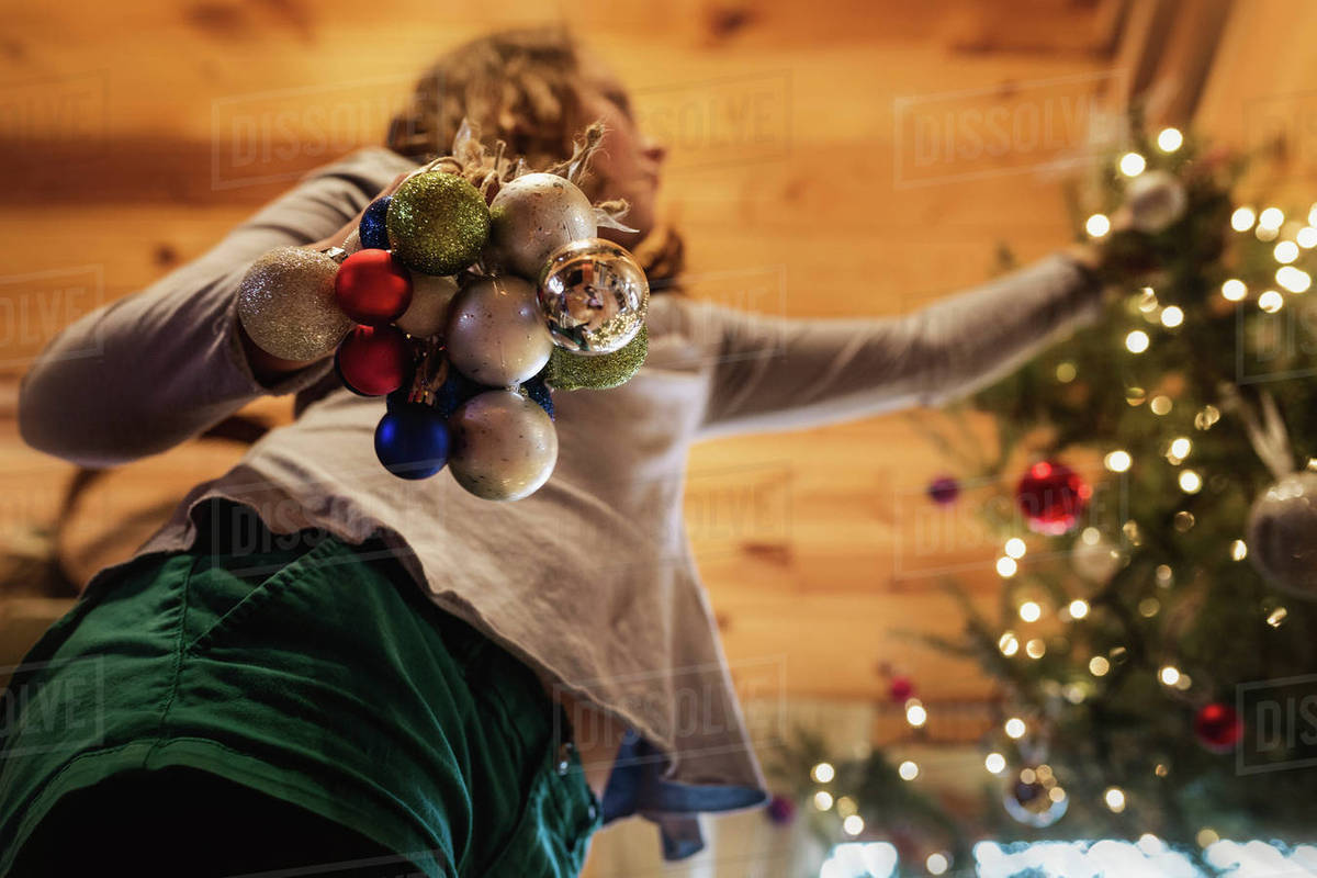 At Home Christmas Trees.Low Angle View Of Girl Decorating Christmas Tree At Home Stock Photo