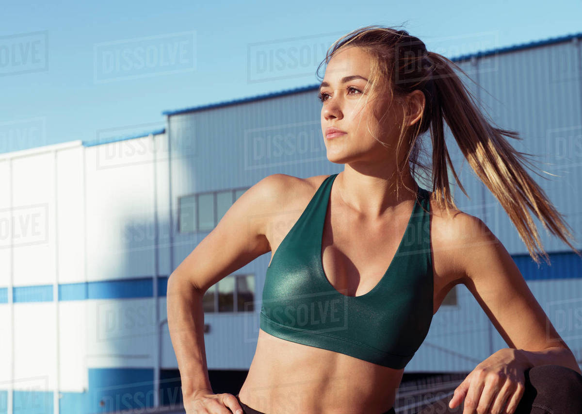 bacee47066 Thoughtful young woman wearing sports bra while standing against buildings  in city
