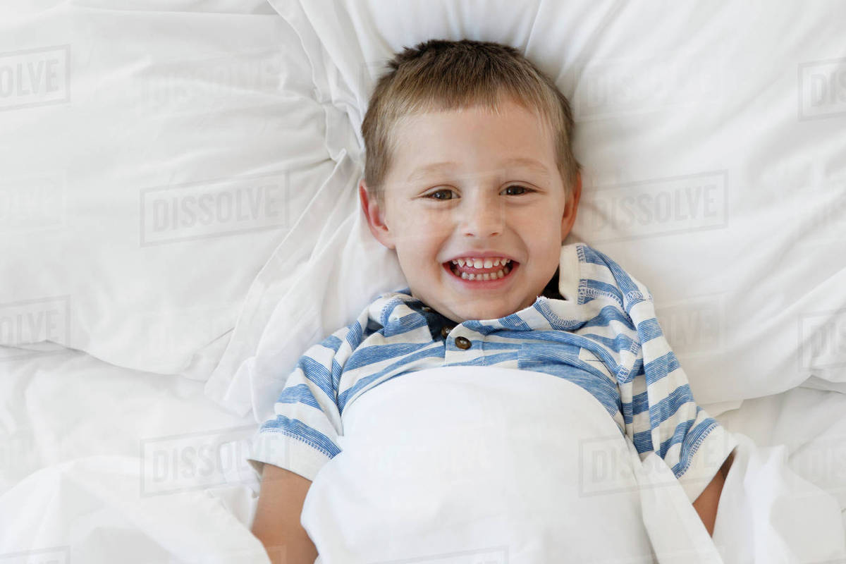 049f75155 Overhead portrait of cheerful boy lying on bed at home - Stock Photo ...