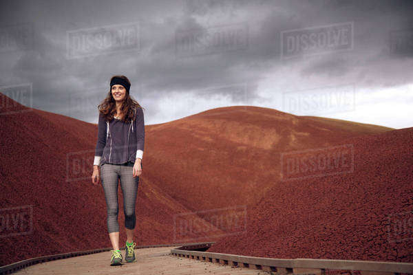 Smiling woman walking on boardwalk amidst barren hills against sky Royalty-free stock photo