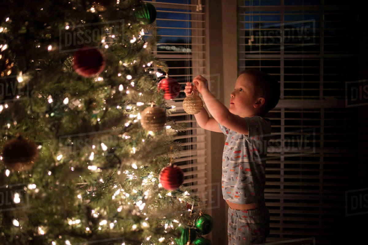 At Home Christmas Trees.Side View Of Boy Hanging Bauble On Illuminated Christmas Tree At Home Stock Photo