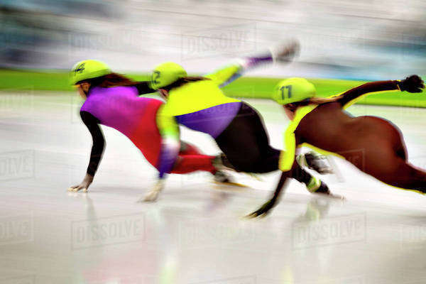 Three female speed skaters rounding track curve during race Royalty-free stock photo