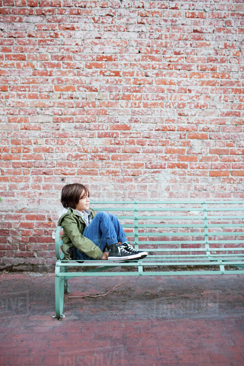 Side View Of Boy Sitting On Bench At Footpath Against Brick Wall