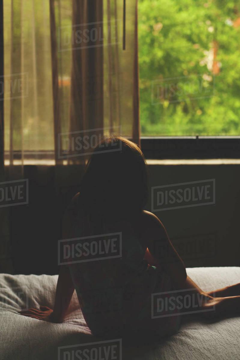 Prime Rear View Of Thoughtful Girl Sitting On Bed In Darkroom D1061 216 039 Spiritservingveterans Wood Chair Design Ideas Spiritservingveteransorg