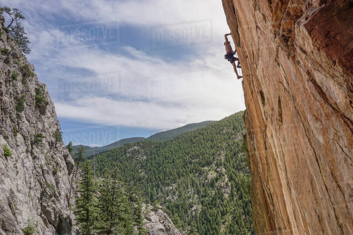 Low angle view of man climbing mountain against cloudy sky Royalty-free stock photo