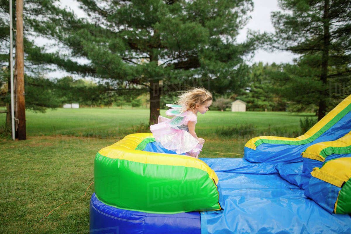 Girl in fairy costume jumping on bouncy castle at park during Halloween Royalty-free stock photo