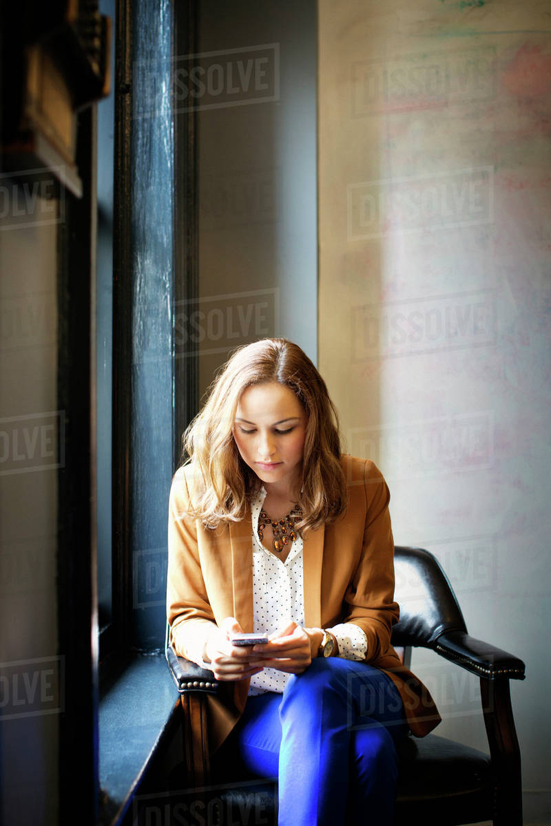 Office worker sitting on armchair by window and using mobile phone on break Royalty-free stock photo