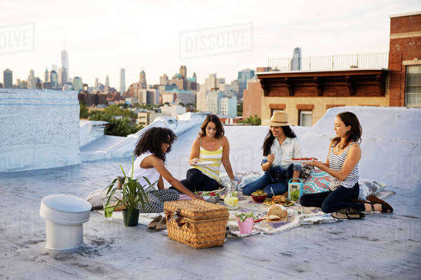 Friends having picnic on rooftop Royalty-free stock photo