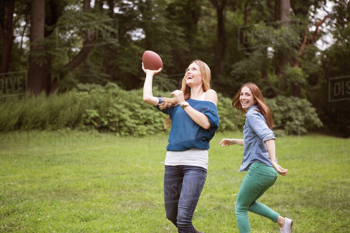 Two friends playing football in park - Stock Photo - Dissolve