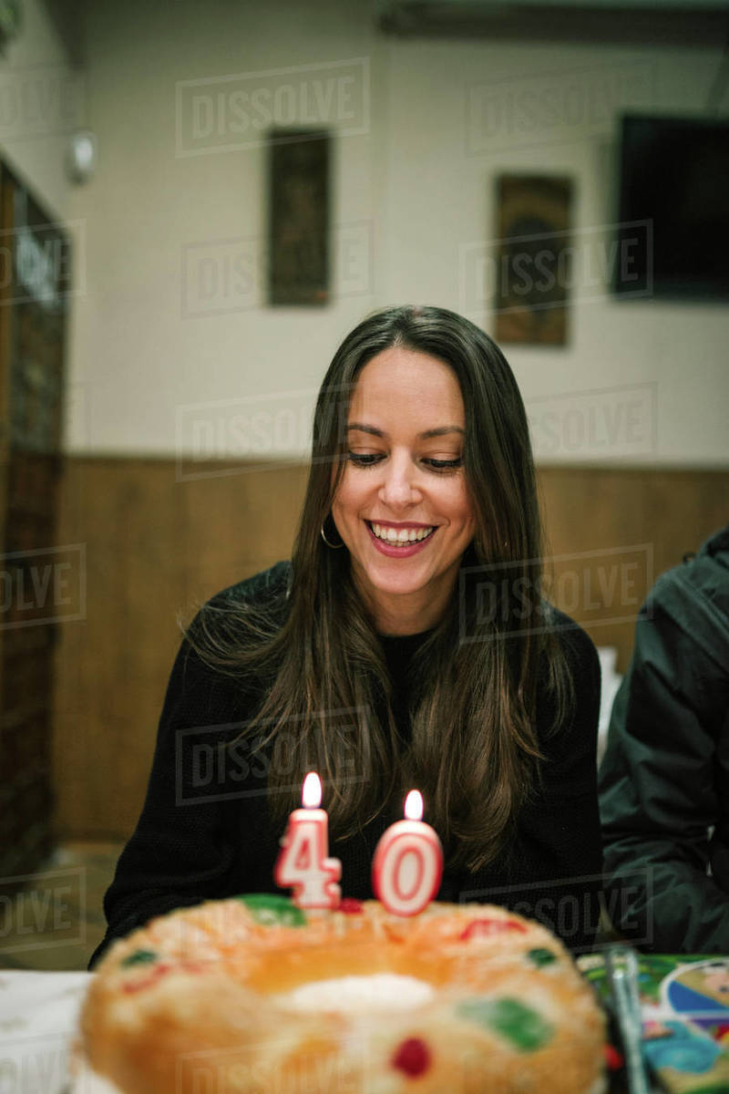 Woman Is Smiling In Front Of A Cake With Candles Her 40th Birthday