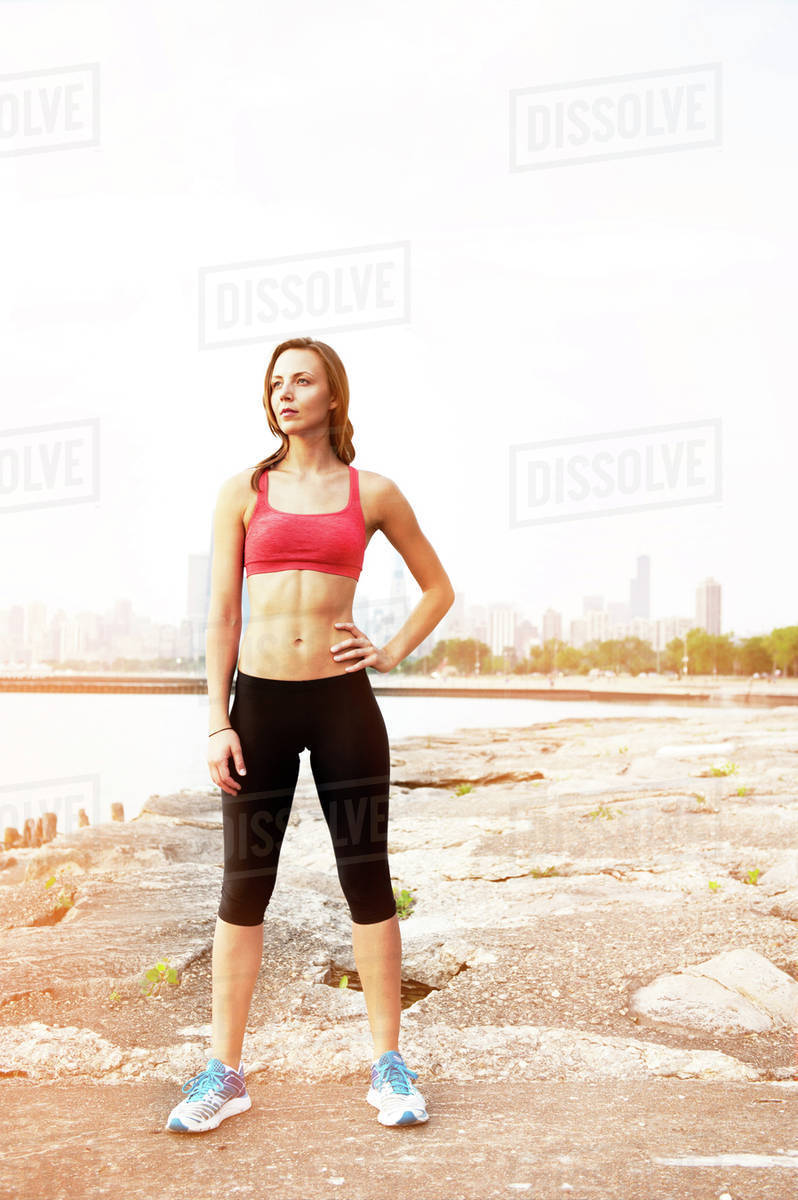 Woman in sports clothing standing by lake Royalty-free stock photo