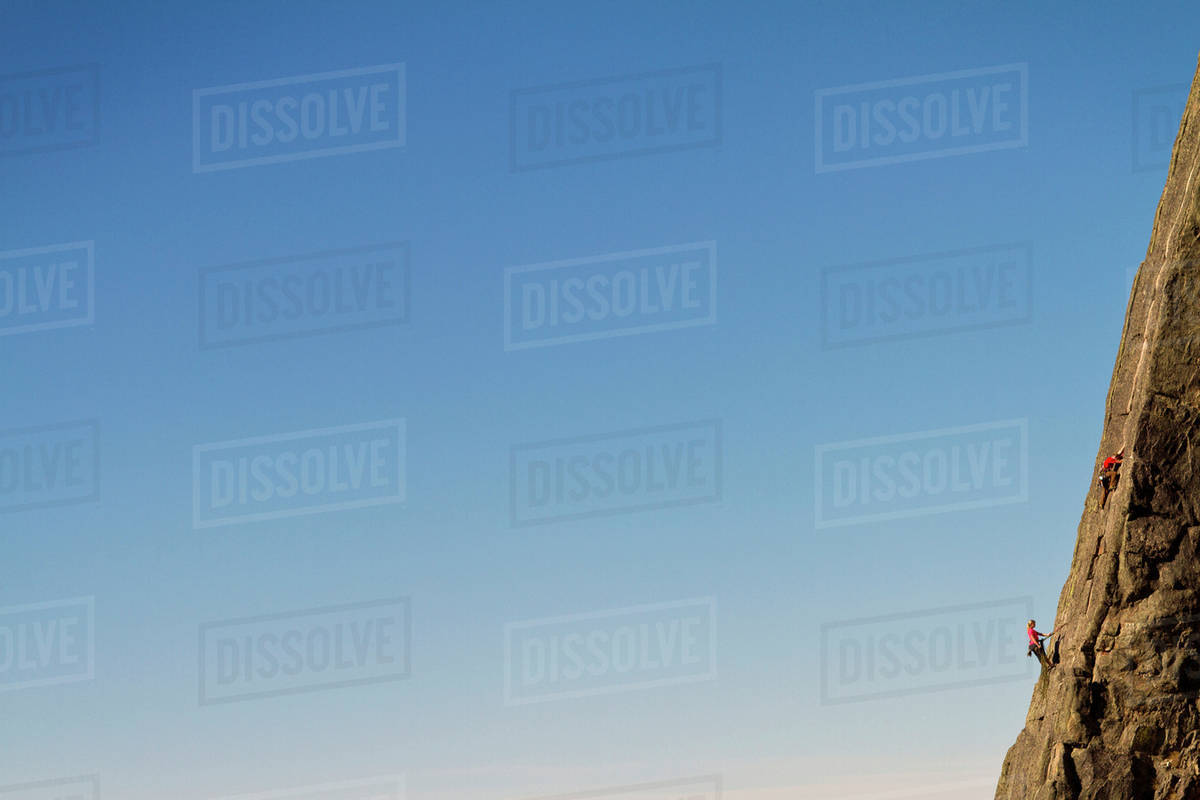 Two people rock climbing with blue sky Royalty-free stock photo