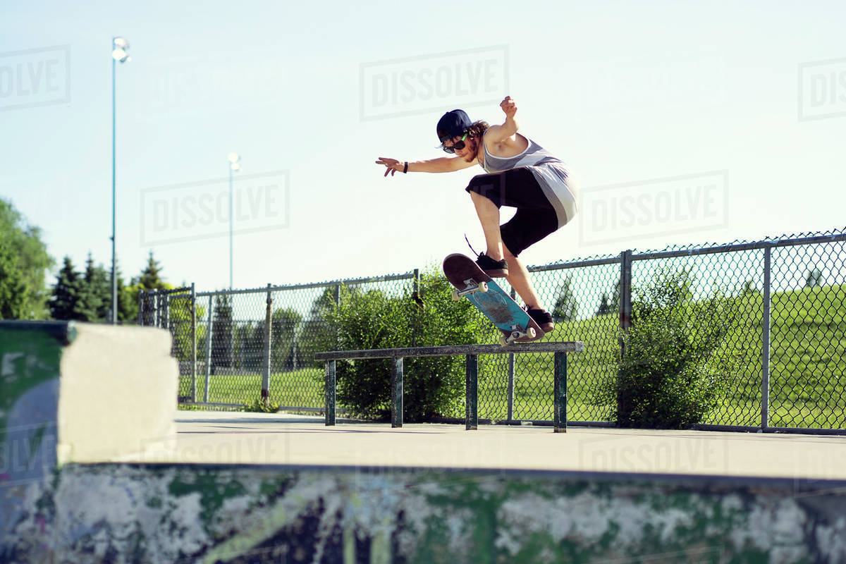 Man jumping from railing with skateboard at park on sunny day Royalty-free stock photo