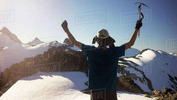 Rear view of man standing with arms raised on snow covered mountain Royalty-free stock photo
