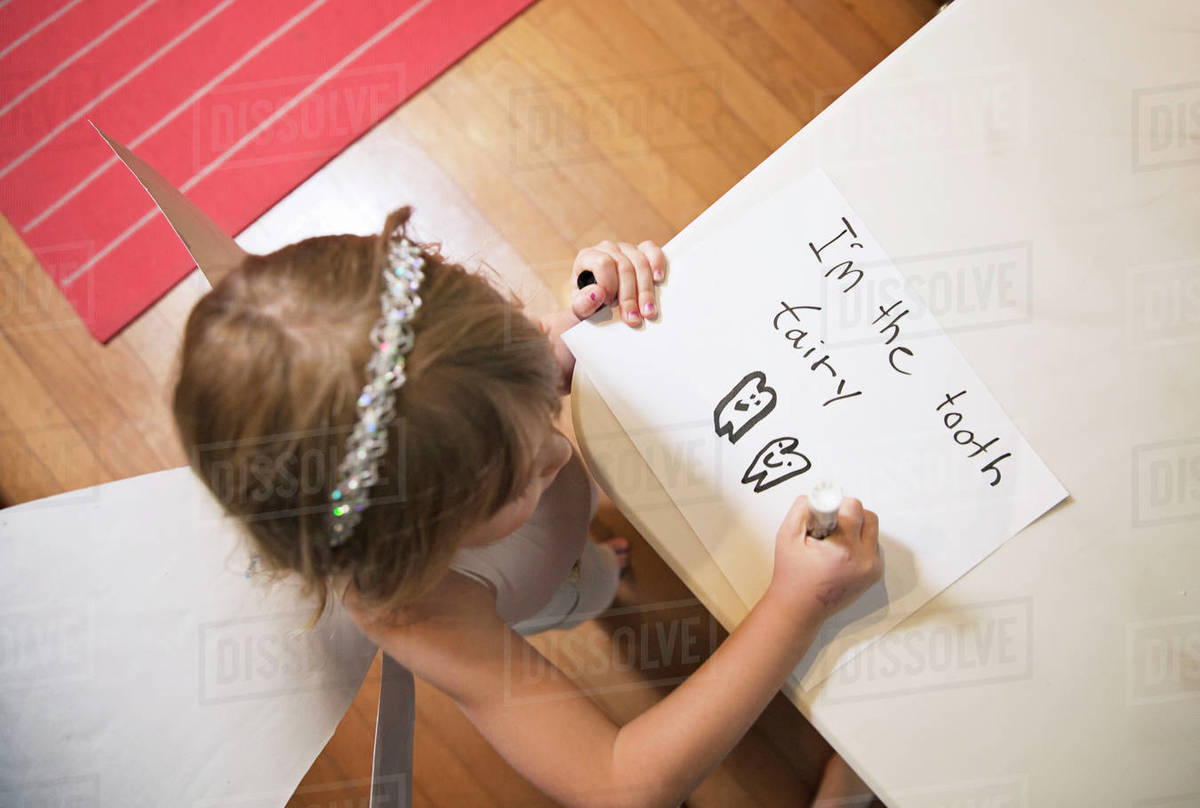 High angle view of girl wearing tooth fairy costume while writing on paper at home Royalty-free stock photo