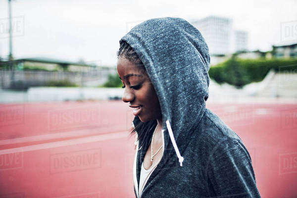 Smiling sportswoman wearing hooded jacket on running tracks Royalty-free stock photo
