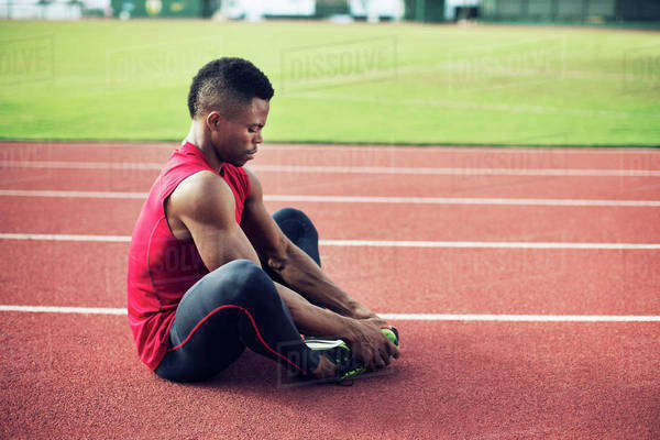Sportsman sitting on running track and stretching Royalty-free stock photo