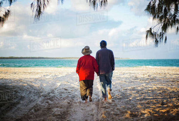 Rear view of senior couple holding hands while walking on sandy beach Royalty-free stock photo