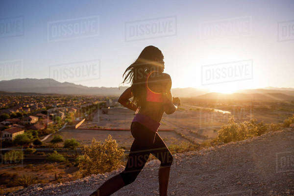 Female athlete jogging on dirt road against clear sky on sunny day Royalty-free stock photo
