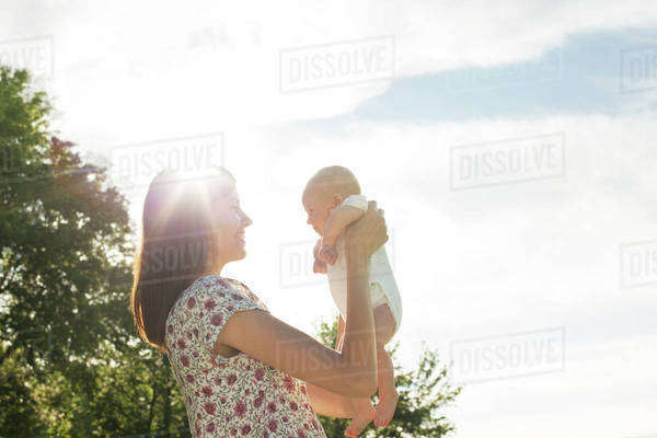 Side view of smiling mother carrying baby against sky on sunny day Royalty-free stock photo