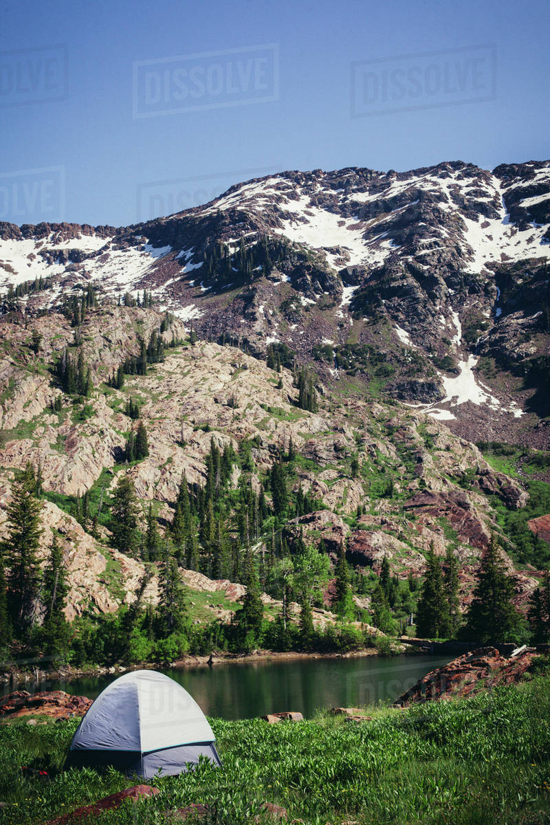 Tent on riverbank, snowcapped mountain in background Royalty-free stock photo