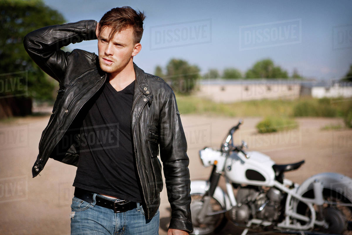 Young Man Wearing Leather Jacket And Motorcycle On Background