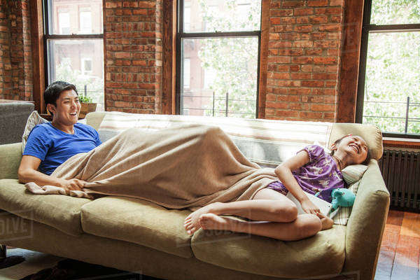 Father and daughter (10-11) lying down on sofa laughing Royalty-free stock photo