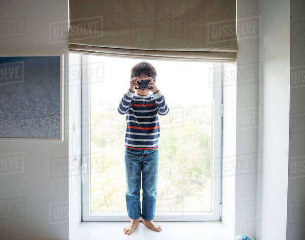 Portrait of boy (6-7) looking through retro camera Royalty-free stock photo