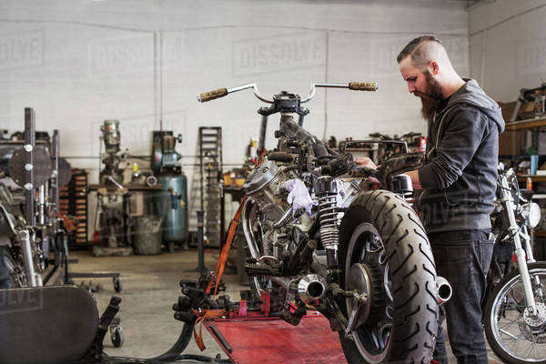 Serious mechanic working on motorcycle at repair shop Royalty-free stock photo