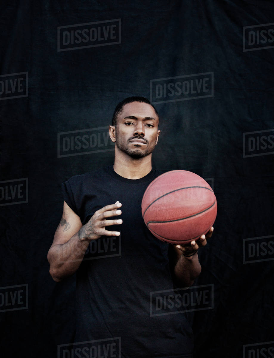 portrait of man holding basketball stock photo dissolve