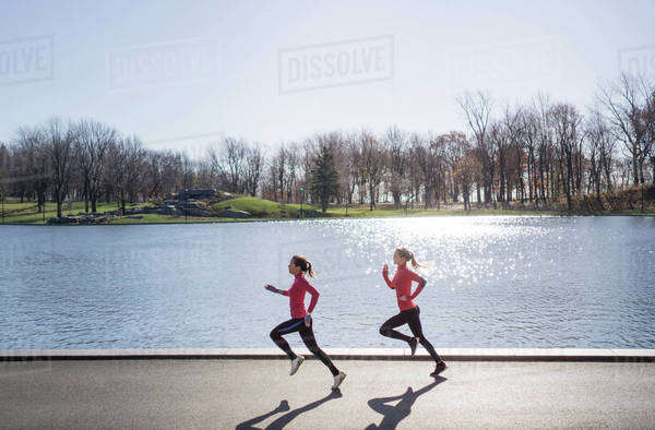 Side view of female friends running on road against lake on sunny day Royalty-free stock photo