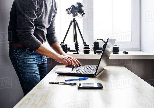 Midsection of man using laptop on table against window Royalty-free stock photo