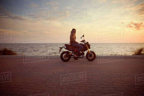 Side view of woman riding motorcycle on street against sea during sunset Royalty-free stock photo