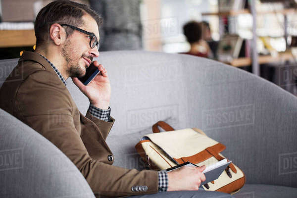 Smiling businessman holding diary while talking on smart phone in restaurant Royalty-free stock photo