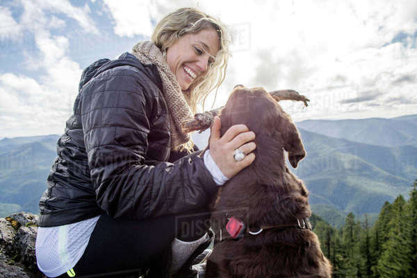 Low angle view of happy woman playing with dog on mountain cliff Royalty-free stock photo