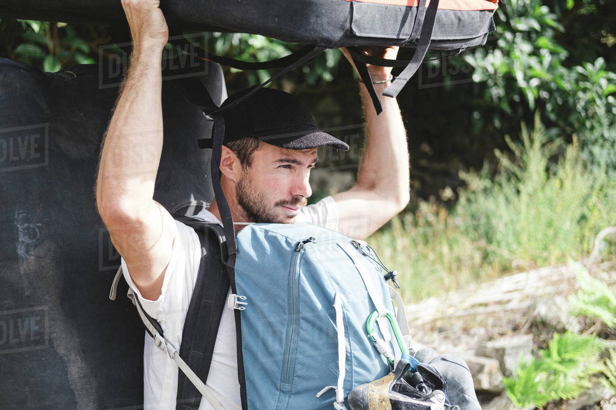 Portrait of a rock climber carrying crashpad and backpacks Royalty-free stock photo