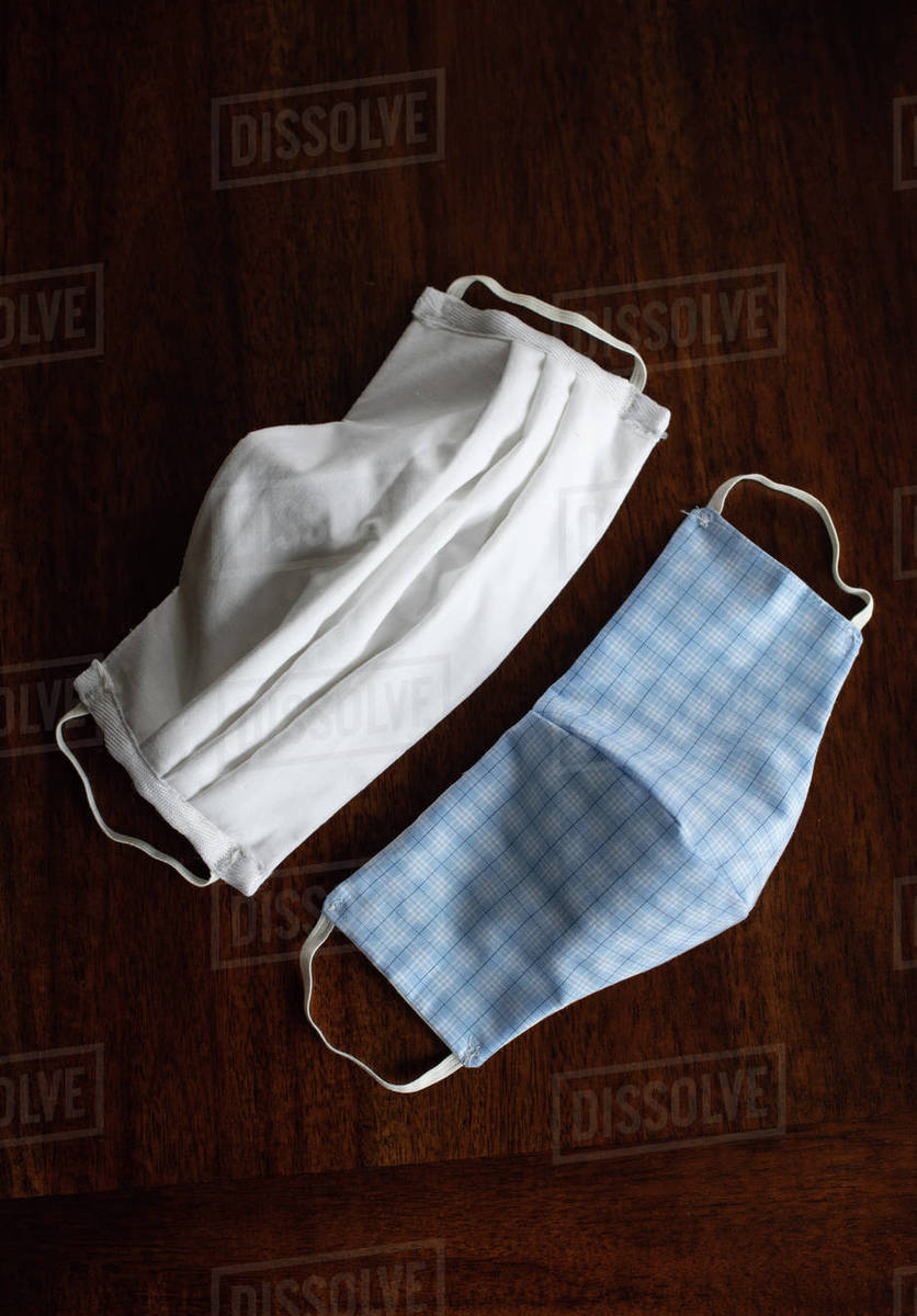 Homemade cloth face masks used during Covid-19 on wood backdrop. Royalty-free stock photo