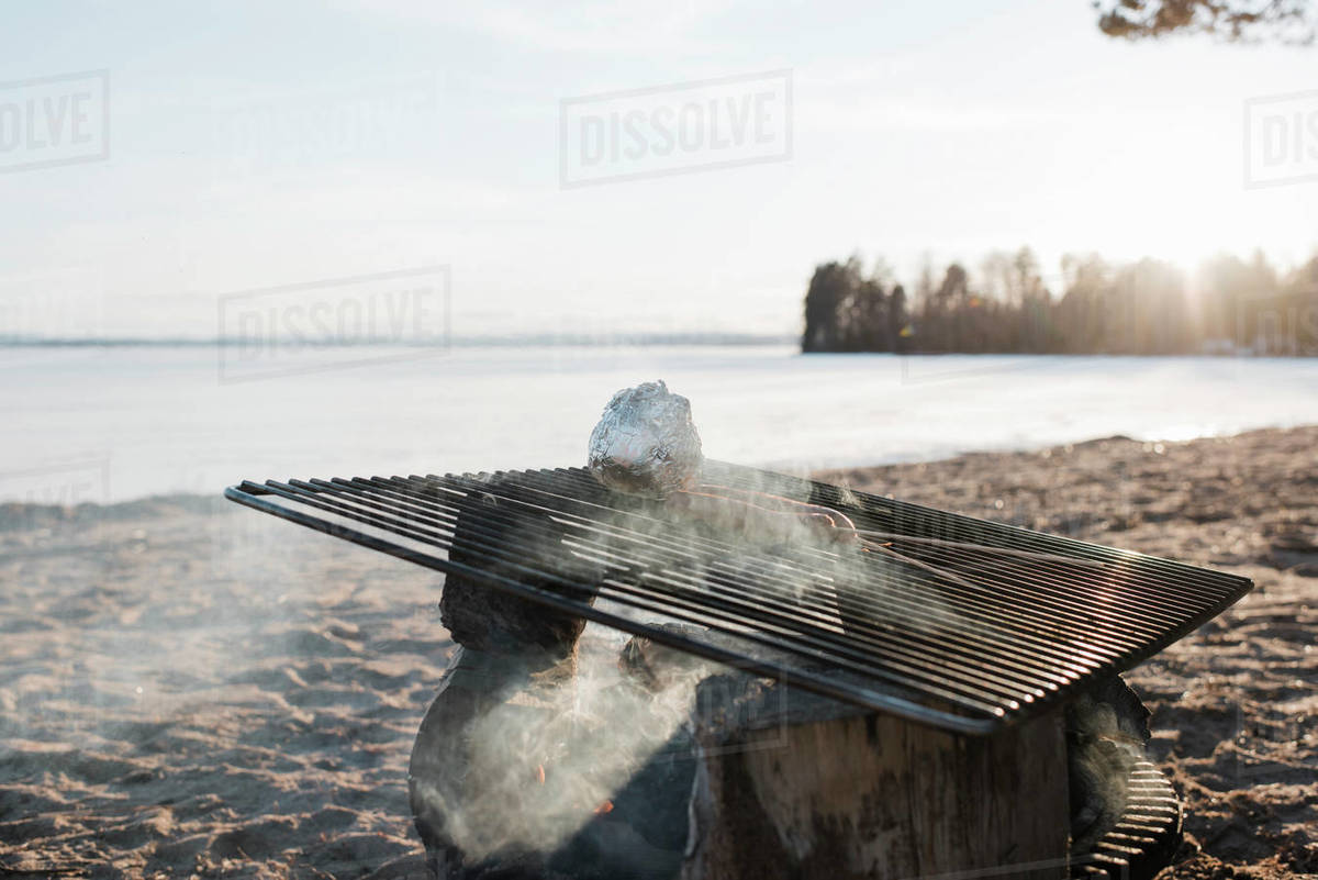 Food cooking on an outdoor fire at the beach at sunset in Sweden Royalty-free stock photo