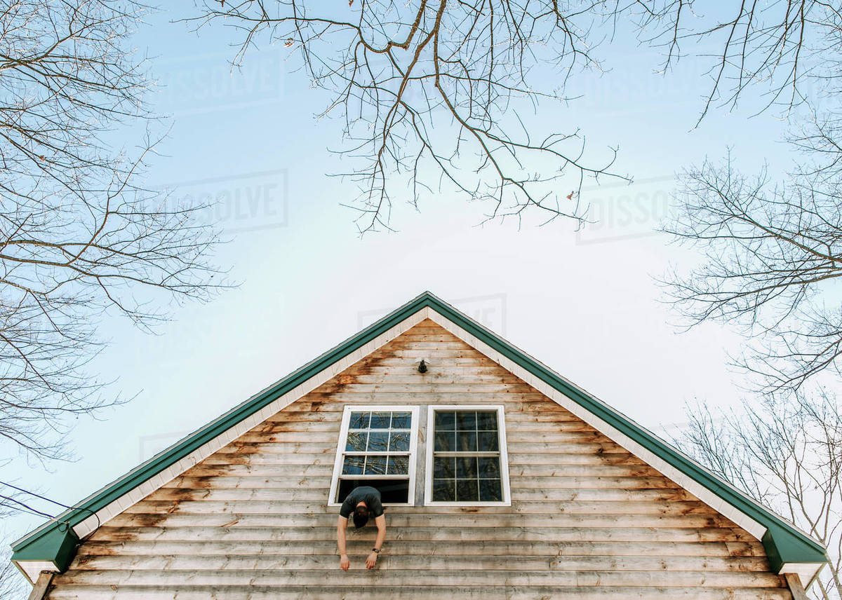 Man hangs limply out of upstairs window of house surrounded by trees Royalty-free stock photo