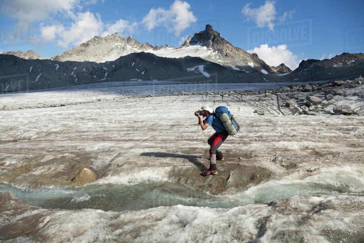 Man takes pictures on Snowbird Glacier, Talkeetna Mountains, Alaska Royalty-free stock photo
