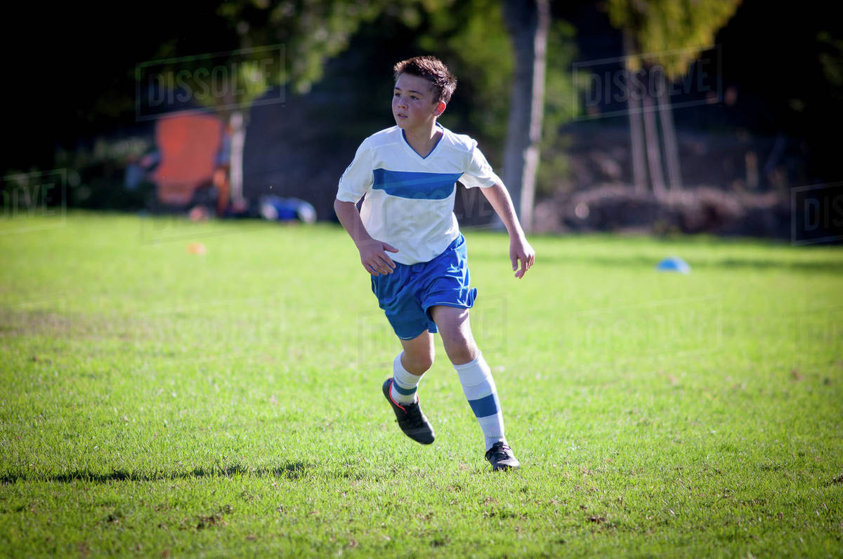 Teen soccer player running on a soccer field Royalty-free stock photo