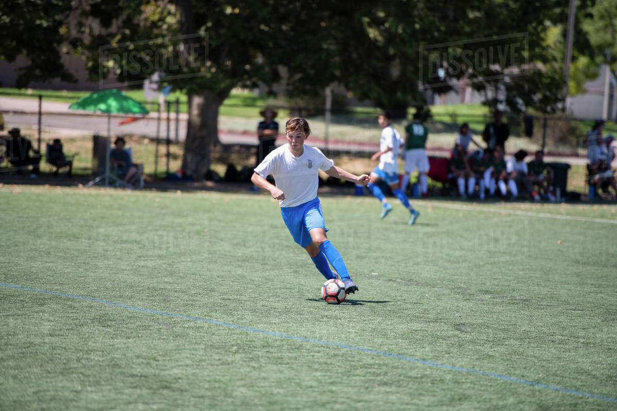 Teen soccer player dribbling the ball during a game Royalty-free stock photo