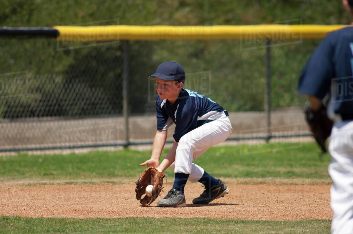 Little League baseball infielder fielding a ground ball Royalty-free stock photo