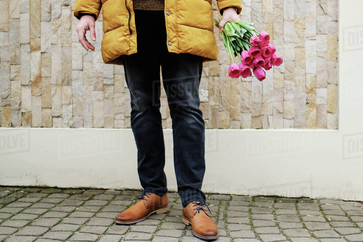 Blond man in a yellow winter jacket with a bouquet of tulips in hands Royalty-free stock photo