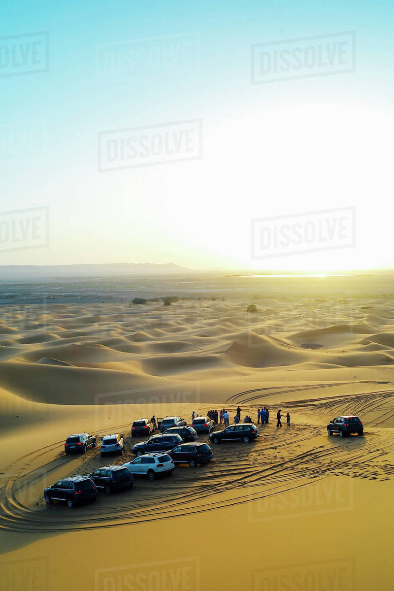 People watch the sunset in the Moroccan desert from their 4x4 cars Royalty-free stock photo
