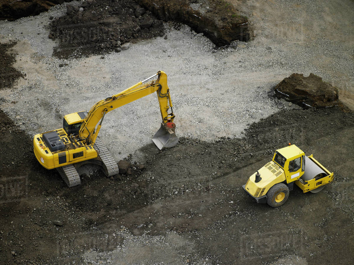 Aerial shot of steamroller and earth mover on building plot Royalty-free stock photo