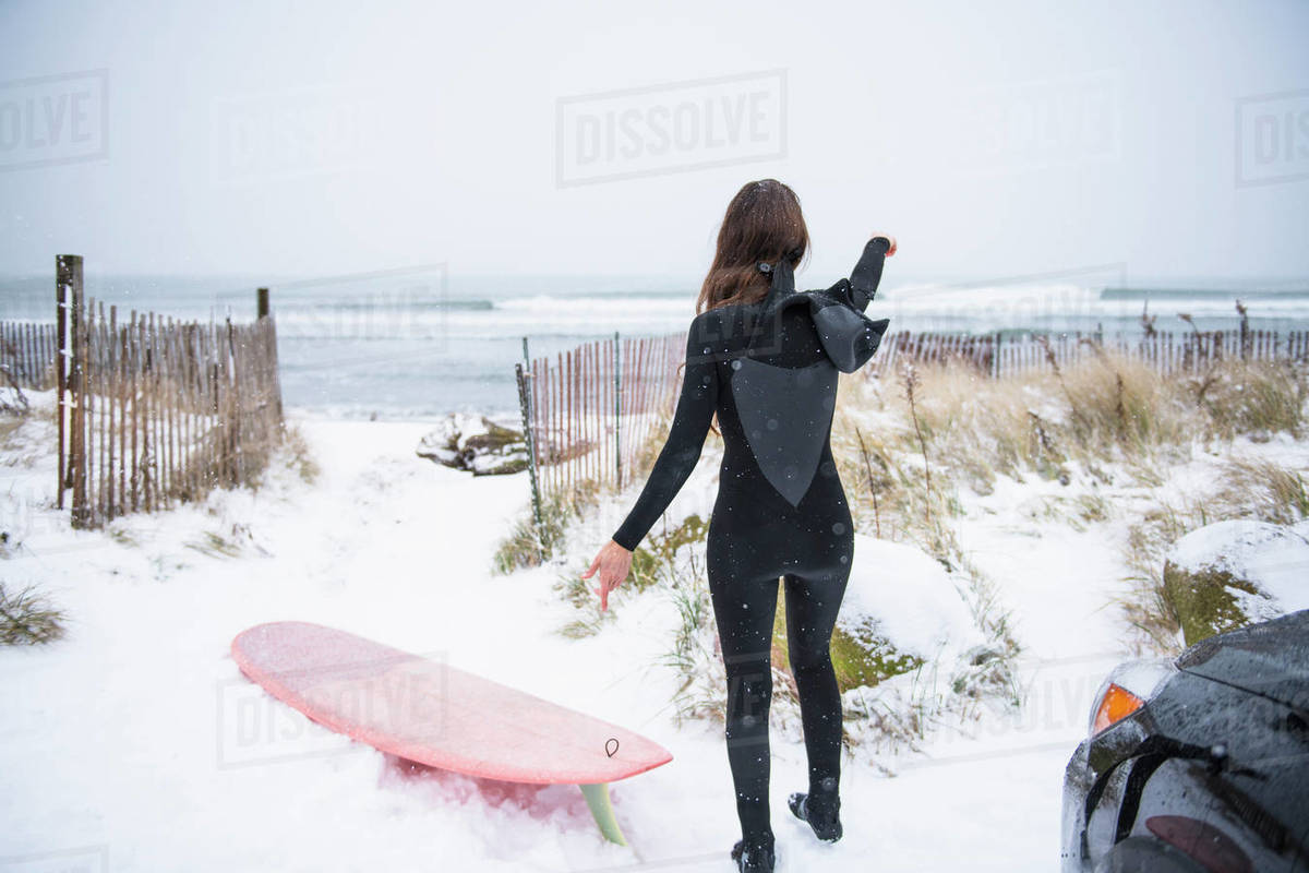 Woman going surfing in winter snow Royalty-free stock photo