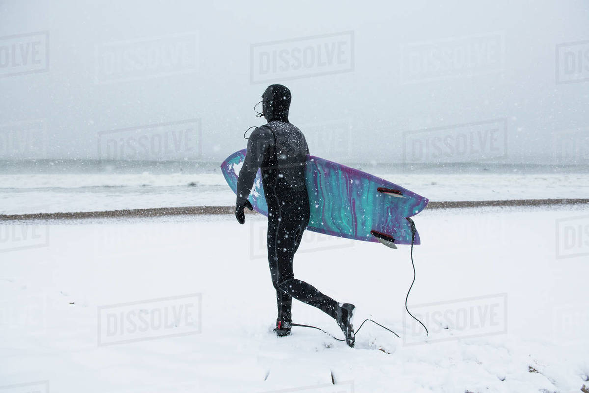 Man preparing to go surfing during winter snow Royalty-free stock photo