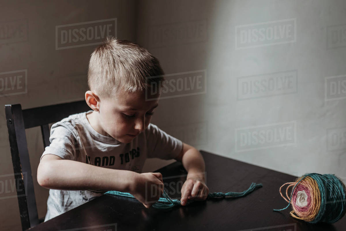 Young boy knitting with fingers at home during isolation Royalty-free stock photo