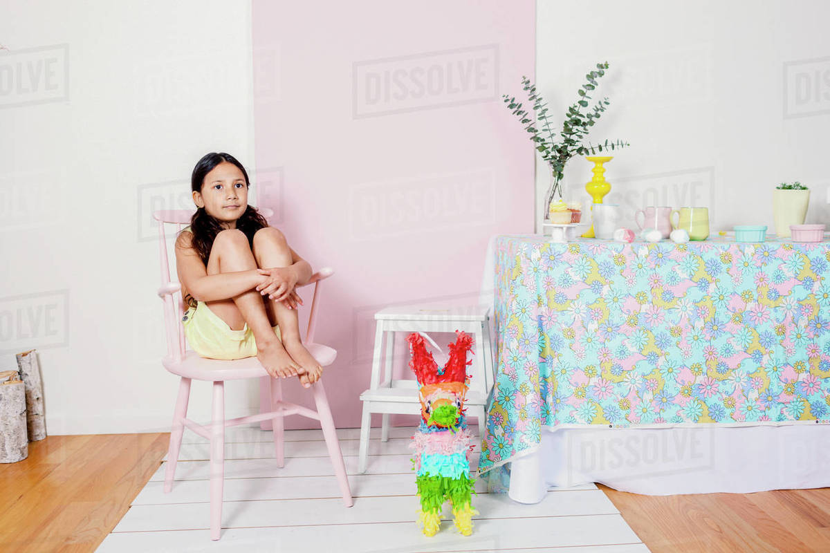 Girl sitting in pink chair at Eastern home party table decor Royalty-free stock photo